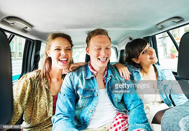 Young teenagers sitting in a taxi.