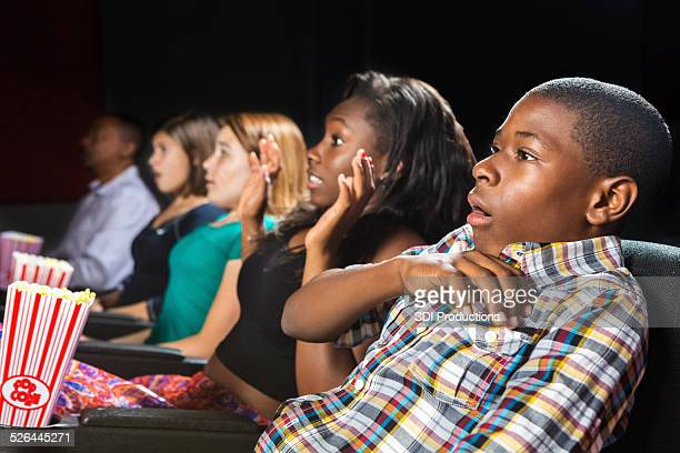 young teens scared by movie in local theater - scary movie stock photos and pictures