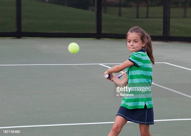 Young tennis player preparing to swing at the green ball