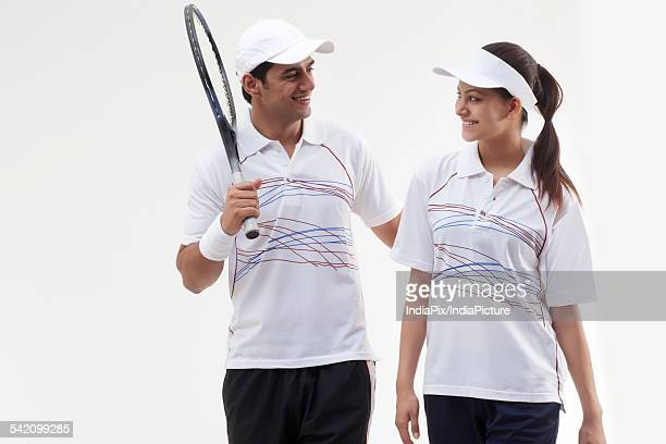 Young tennis players looking at each other against white background