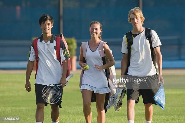 Young tennis players walking with equipment