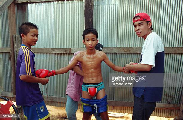 A young Thai boxer gets prepared for a bareknuckle fight in a boxing ring at an amusement park in Mae Sot Children fight for as little as 300 baht...