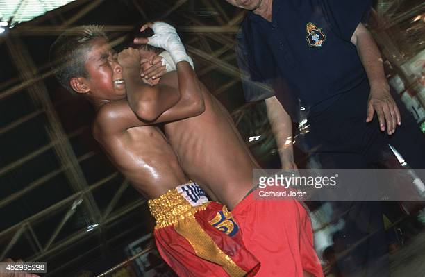 A young Thai boxer locked in battle with his Burmese opponent in a fight in a shack at the ThaiBurmese border in Mae Sot Adult bouts have five...
