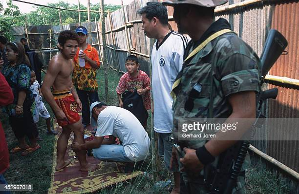 A young Thai boxer outside a shack that is holding a boxing event at the ThaiBurmese border in Mae Sot A Thai border policeman looks on Adult bouts...
