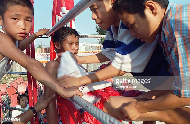 A young Thai boxer sits slumped in a chair between rounds in the ring at an amusement park in Mae Sot Children under fifteen fight for three...