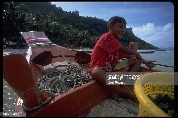 A young Thai boy sits on a boat near the anchor in the Ang Thong National Marine Park in the Gulf of Thailand   Location Ang Thong National Marine...