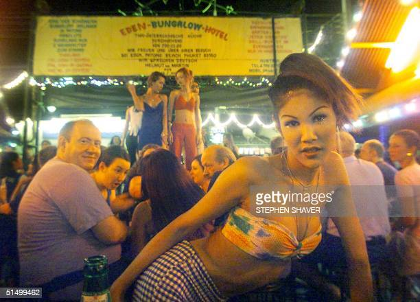 A young Thai ladyboy or transvestite smiles and dances 'her' way through a crowd of foreign tourists as others dance on a stage at Phuket's garishly...