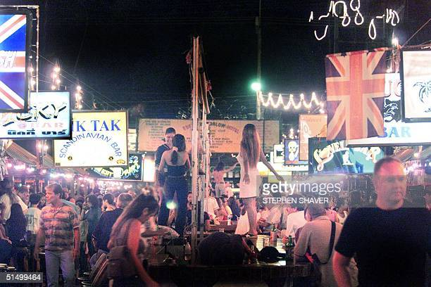 Young Thai ladyboys or transvestites dance on a long bar table as foreign men drink and walk around Phuket's garishly overdeveloped Patong Beach 21...