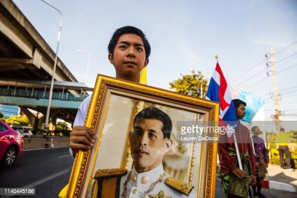 A young Thai man holds a portrait of King Rama X in a Labor Day parade on May 1 2019 in Bangkok Thailand The Thai Ministry of Labor organized a march...