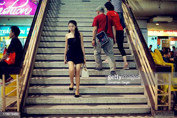 Young Thai woman in a black dress walking down a flight of stairs in Golden Mile, a Thai shopping mall.