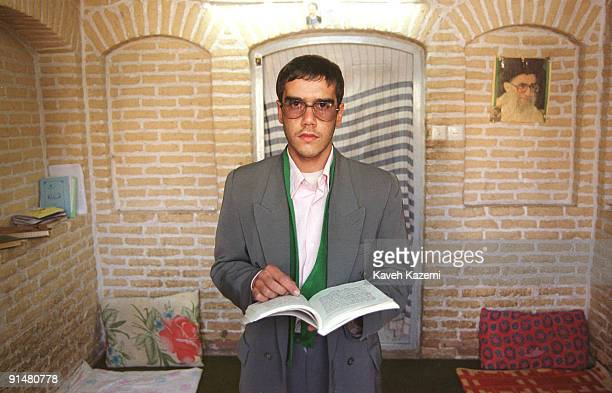 Young theology student at a seminary in Yazd, Iran, with a picture of Ayatollah Ali Khamenei on the wall behind him, 20th December 1999.