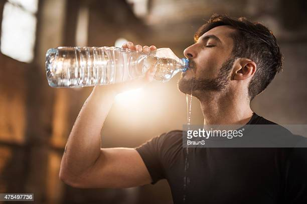 Young thirsty athlete drinking water after exercising.