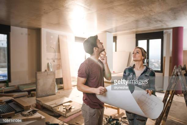 young thoughtful couple with blueprints inside of renovating apartment. - rebuilding stock pictures, royalty-free photos & images