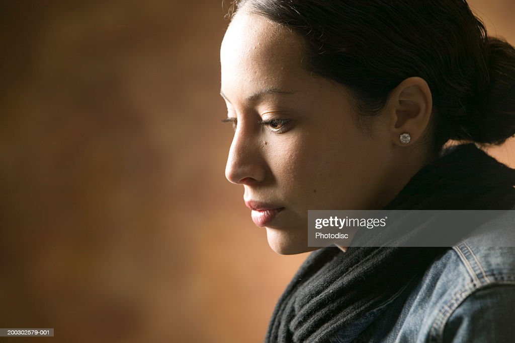 Young thoughtful woman posing in studio, close-up, portrait : Stock Photo