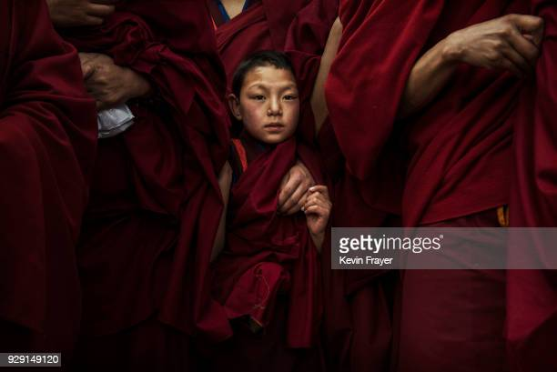 A young Tibetan Buddhist Monk of the Gelug or Yellow Hat school waits before a procession to unveil a giant thangka showing the Buddha on a hillside...