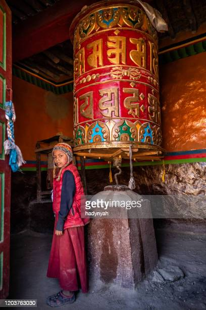 a young tibetan buddhist monk turning the prayer wheels, lo manthang, upper mustang, nepal - nepal imagens e fotografias de stock
