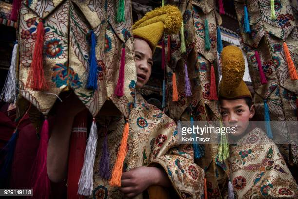 Young Tibetan Buddhist Monks of the Gelug or Yellow Hat school wait before a procession to unveil a giant thangka showing the Buddha on a hillside...