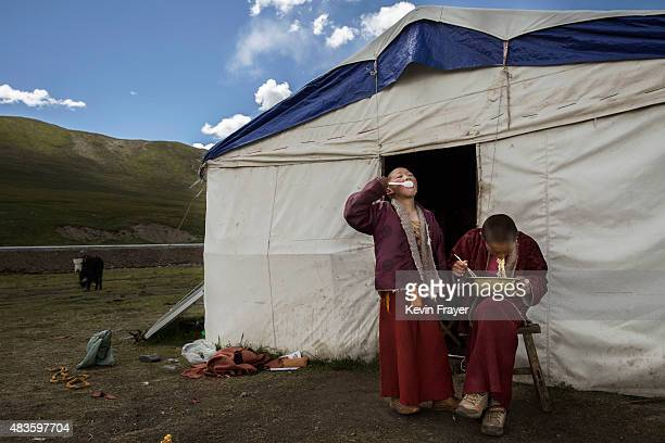 Young Tibetan Buddhist novice monks eat outside a tent at the family's nomadic summer grazing area on July 23 2015 on the Tibetan Plateau in Yushu...