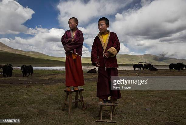 Young Tibetan Buddhist novice monks stand outside the family's nomadic summer grazing area on July 24 2015 on the Tibetan Plateau in Yushu County...