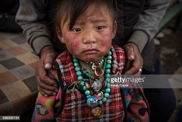 A young Tibetan child from a poor family sits in a tent at a temporary camp for cordycep pickers on May 23 2016 on the Tibetan Plateau near Zadoi in...