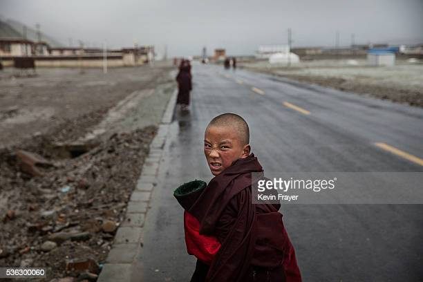 A young Tibetan monk walks on a road on May 20 2016 near Sershul an area well known for cordycep harvesting on the Tibetan Plateau in the Garze...