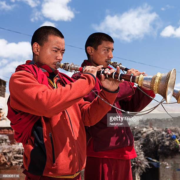 young tibetan monks playing buddhist horns on the roof, lomanthang - red tube top stock photos and pictures