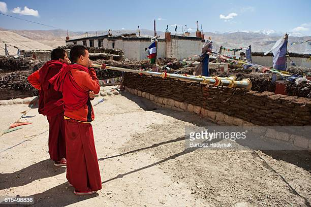 young tibetan monks playing buddhist horns on the roof, lomanthang - lo manthang stock pictures, royalty-free photos & images