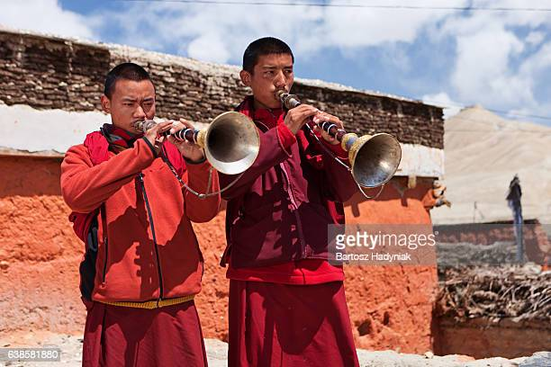 Young Tibetan monks playing buddhist horns on the roof, LoManthang