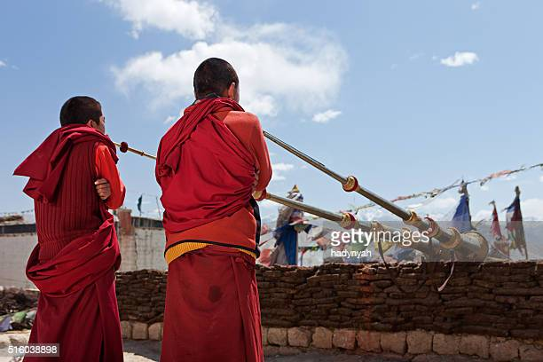 Young Tibetan monks playing buddhist horns on the roof, Mustang