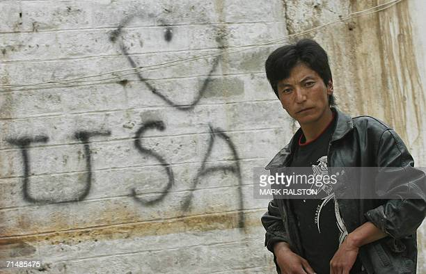 A young Tibetan musician walks past a piece of pro USA grafitti near the Jokhang Temple in the Tibetan capital Lhasa 06 July 2006 The country is...