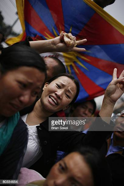 A young Tibetan woman standing in front of a Tibetan flag make a peace symbol during a Tibetan peace rally in front of the United Nations building on...