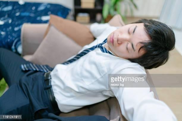 若い疲れたビジネスマンはソファで眠りに落ちた - 疲れている ストックフォトと画像