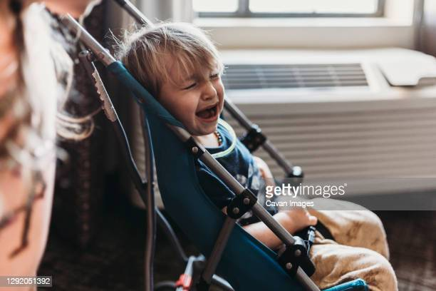 young toddler boy crying in his stroller in hotel room in palm springs - carriage stock pictures, royalty-free photos & images