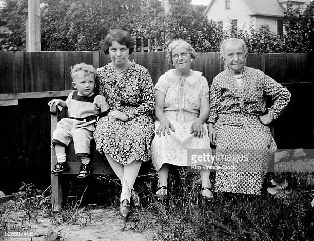 Young toddler boy poses with his mother grandmother and great grandmother in the backyard of his Ohio home