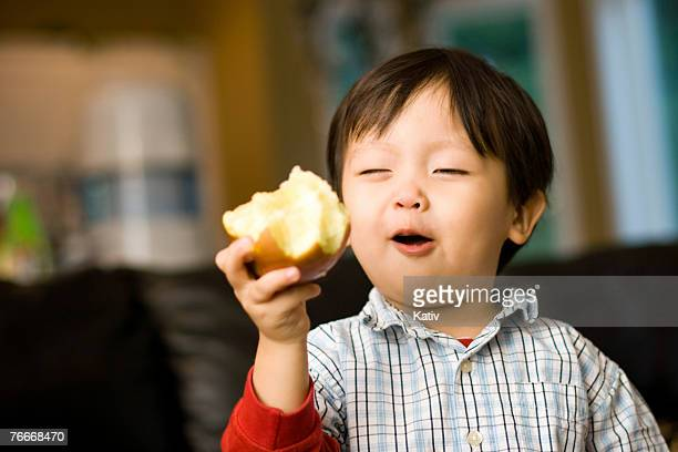 Young toddler eating an apple and loving it.