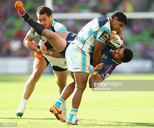 Young Tonumaipea of the Storm is tackled by Brad Takairangi and Albert Kelly of the Titans during the round five NRL match between the Melbourne...