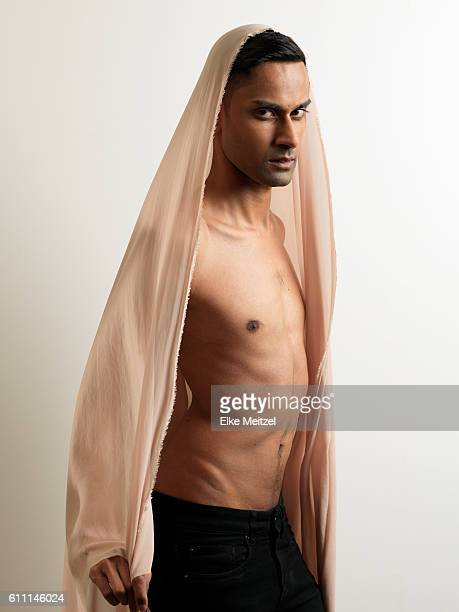 young topless male enveloped in dusty pink fabric