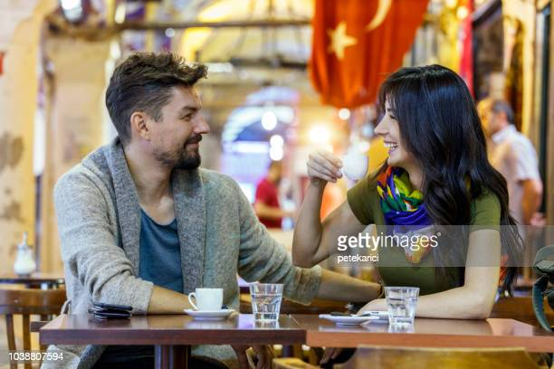 Young tourist couple drinking Turkish coffee in Grand Bazaar, Istanbul, Turkey
