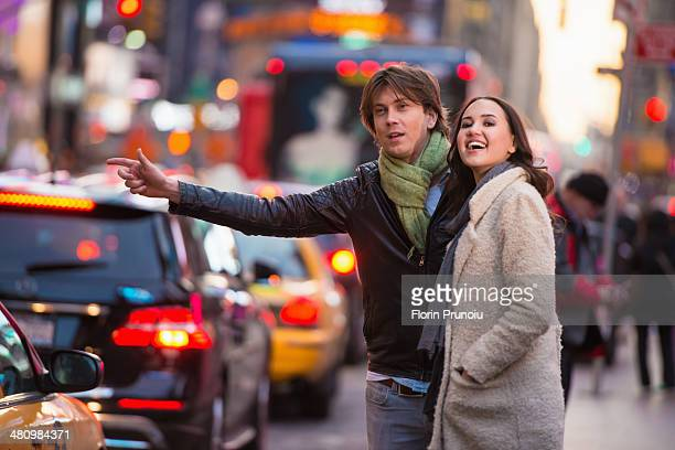 Young tourist couple hailing a cab, New York City, USA