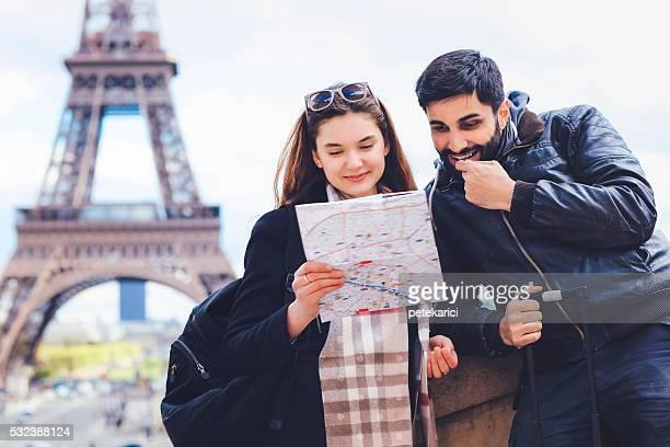 Jeune couple de touristes regardant carte, de la tour Eiffel