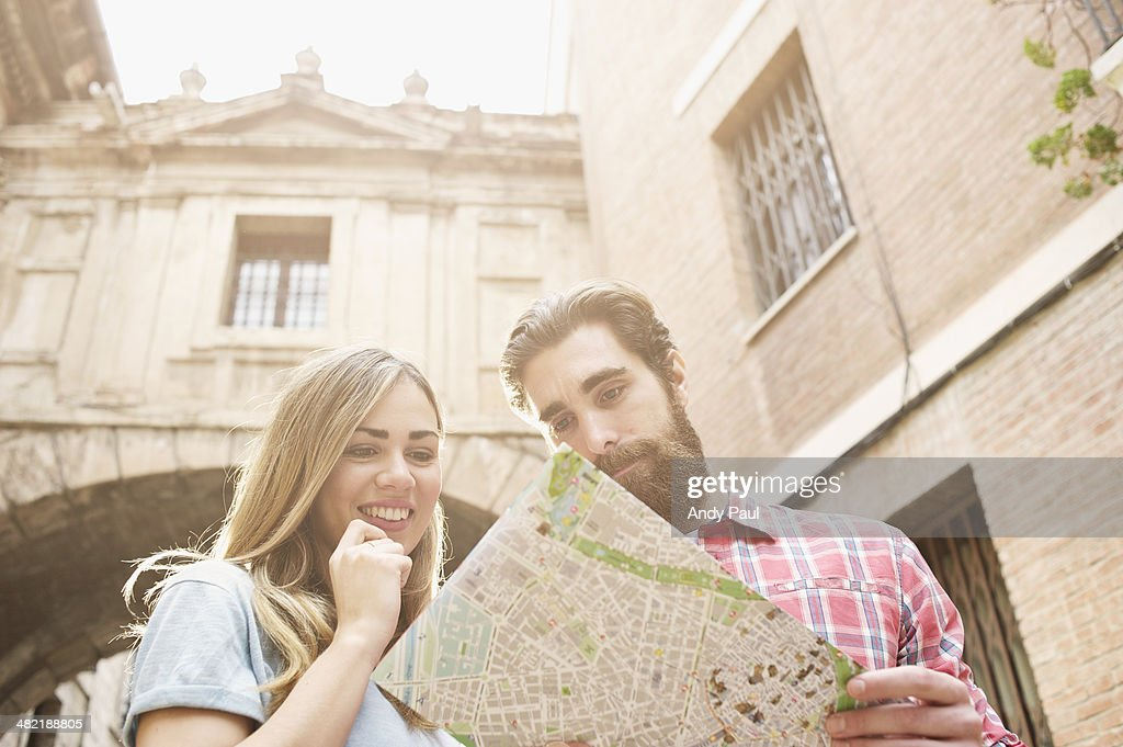 Young tourist couple looking at map outside Valencia Cathedral, Valencia, Spain : Stock Photo
