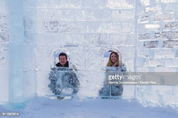 A Young Tourist Couple Poses Inside Of An Ice Castle Build On The Ice At Lake Louise In Banff National Park