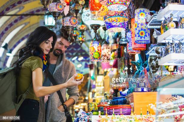 young tourist couple shopping in in grand bazaar, istanbul, turkey - turkey middle east stock pictures, royalty-free photos & images