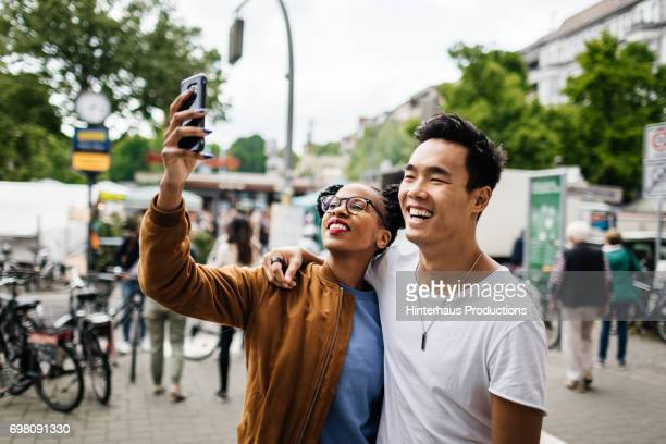 young tourist couple taking a photo of themselves - wereldreis stockfoto's en -beelden