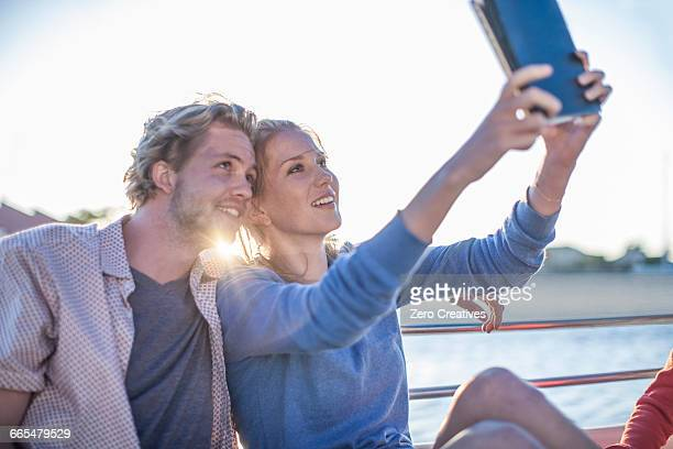 Young tourist couple taking digital tablet selfie on boat trip, Cape Town, South Africa