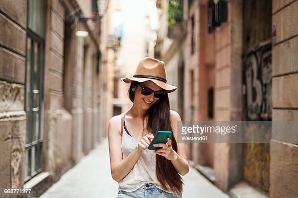 Young tourist discovering streets of Barcelona, using mobile phone