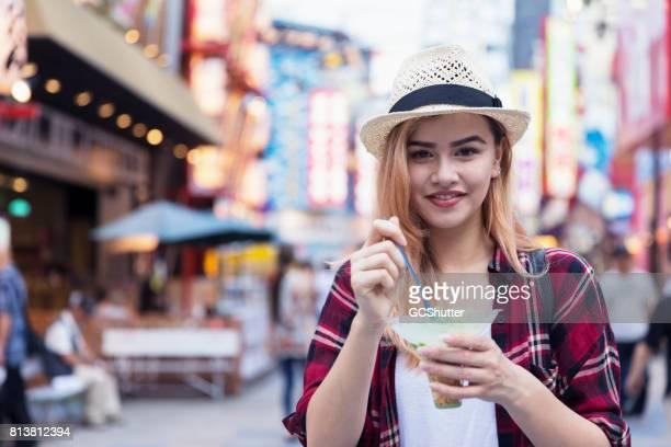 Young tourist enjoying ice cream as she walks down Shinsekai Street