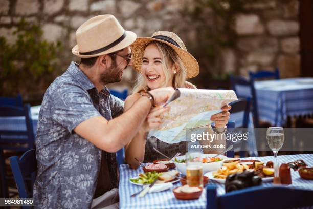 young tourist friends reading map at traditional restaurant in spain - greece stock pictures, royalty-free photos & images
