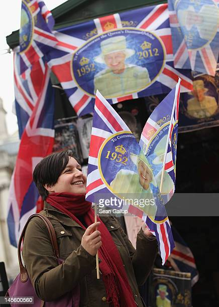A young tourist from Austria holds souvenir flags commemorating the Diamond Jubilee of Queen Elizabeth II she had just bought at Trafalgar Square on...