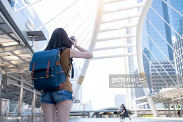 young tourist girl standing taking a picture in the city - vogue stock pictures, royalty-free photos & images